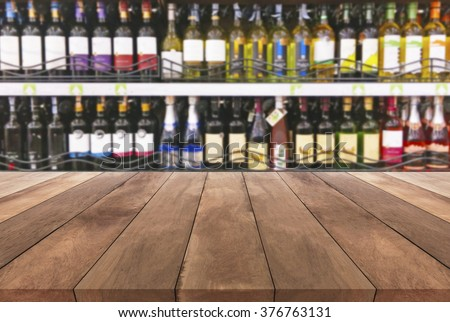 Wood table and wine Liquor bottle on shelf  Blurred background - stock photo