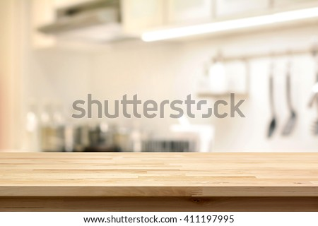 Wood table top (as kitchen island) on blur kitchen interior background - can be used for display or montage your products - stock photo
