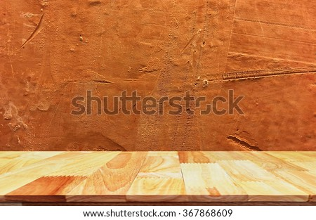 Wood table top on bare concrete wall background