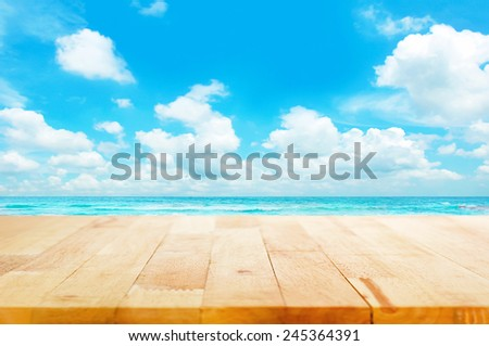 Wood table top on blue sea & sky background can put or montage your products for display - beach & summer concepts - stock photo