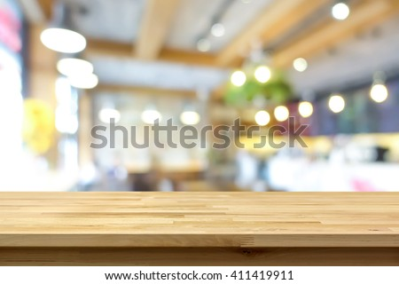 Wood table top on blur background of coffee shop (or restaurant) interior - can be used for display or montage your products - stock photo