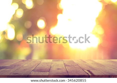 Wood table top on blur bokeh background of sunlight shining through the trees - can be used for display or montage your products - stock photo