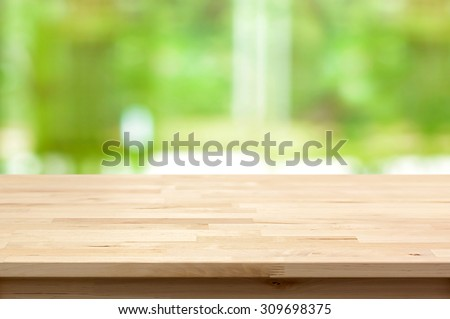 Wood table top on blur green background - can be used for montage or display your products - stock photo