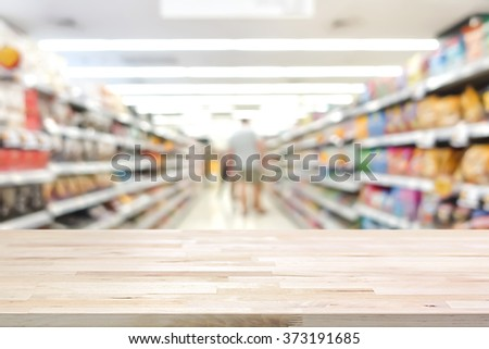 Wood table top on blur supermarket background - can be used for display or montage your products - stock photo
