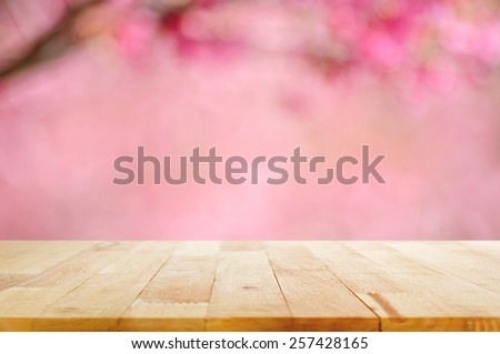 Wood table top on blurred background of pink cherry blossom flower - can used for display or montage your products - stock photo