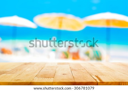 Wood table top on blurred beach background, summer holiday background concept  - can be used for montage or display your products - stock photo