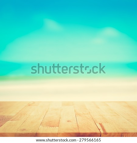 Wood table top on blurred beach background, vintage tone - can be used for display or montage your products - stock photo