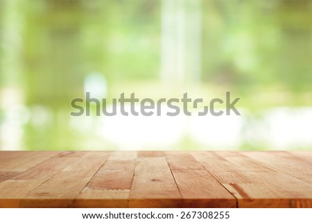 Wood table top on blurred green background - can be used for montage or display your products - stock photo