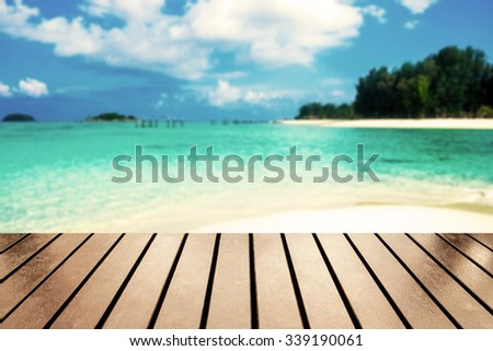 Wood table top on blurred sea beach white sand on andaman sea