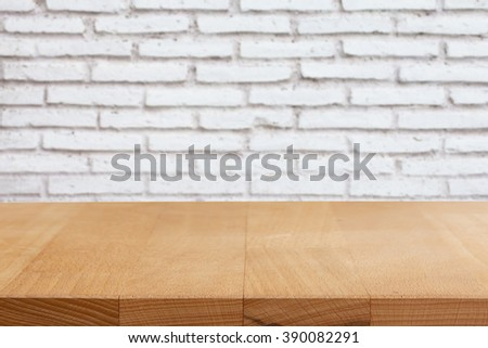 Wood table top on brick wall background. - stock photo