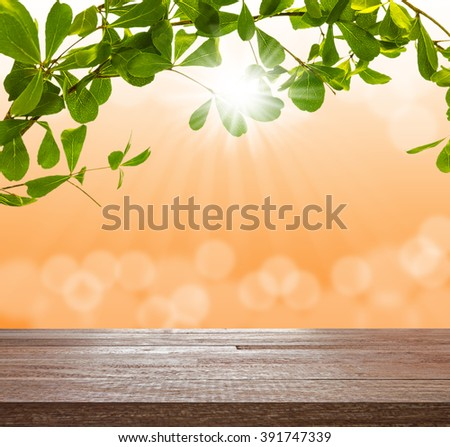 Wood table top on green tree with blurred light bokeh and sunray in color of sunrise, Can be used for display or montage your products - stock photo