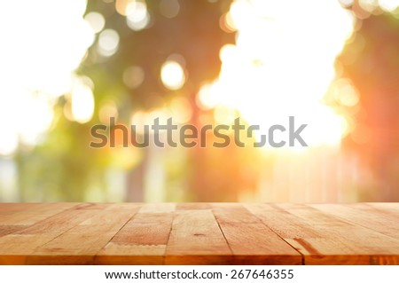 Wood table top on shiny sunlight bokeh background - can used for display or montage your products - stock photo
