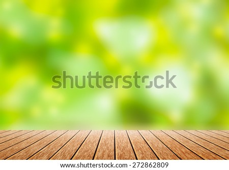 Wood table top with blur green nature bokeh background.can use for magazine or put any word on it - stock photo