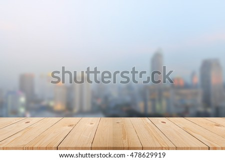 Wood table top with blurred city scape as background