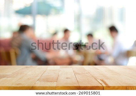 Wood table top with blurred people in cafe as background - can be used for montage or display your products - stock photo