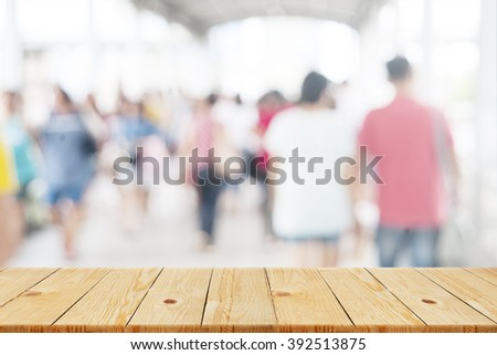 Wood table top with blurred shopping mall as background - can be used for montage or display your products - stock photo