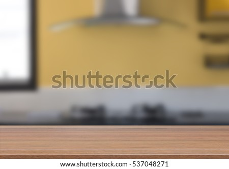 Wood table top with modern yellow kitchen room interior