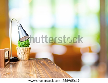 Wood table with lamp and picture frame at blurred garden cafe background - stock photo