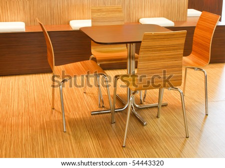 wood table with several chairs near by - stock photo