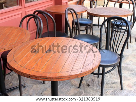 wood tables and black chairs set up for lunch outside cafe - stock photo