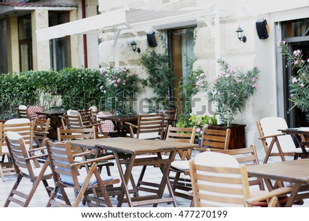 Wood tables, wood chair  and flowers at the restaurant. Restaurant exterior. Terrace.