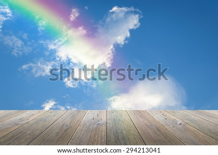 Wood terrace and Blue sky and white cloud with rainbow - stock photo