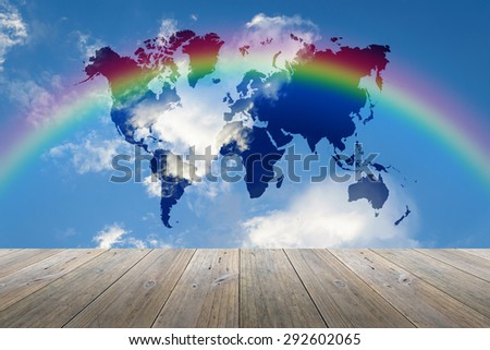 Wood terrace and Blue sky background with world map and rainbow - stock photo