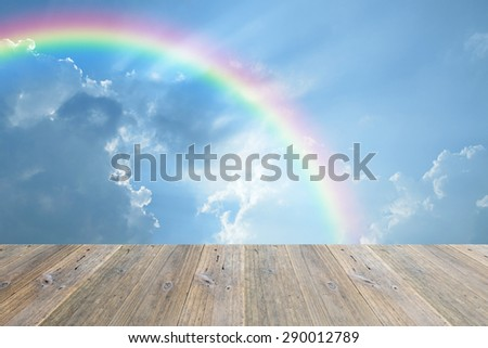 Wood terrace and nature cloudscape with blue sky and white cloud with rainbow - stock photo