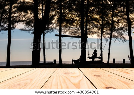 Wood terrace with silhouette of a girl sitting on the swing during sunset on the beach - stock photo