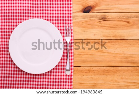 Wood texture background. Cutlery on red checkered tablecloth tartan. Wooden table close up view from top. Wooden kitchen cutting board retro. Product pages for installation recipe books menu  - stock photo