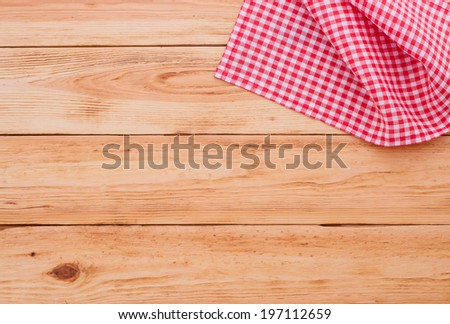 Wood texture background. Pure notebook for recording menu, recipe on red checkered tablecloth tartan. Wooden table close up view from top. Empty wooden deck table with tablecloth for product montage.  - stock photo