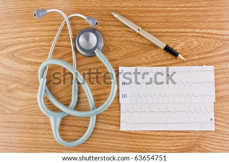 Wood texture background with stethoscope or phonendoscope ECG electrocardiogram graph and elegant pen