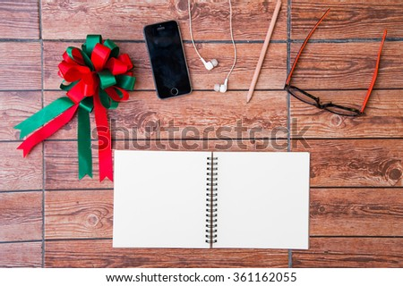 Wood texture mock up with notebook, ribbon, smart phone, earphone, pencil and glasses. View from above. Christmas Day. - stock photo