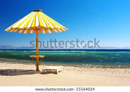 Wood umbrella on beach with clear blue sky - stock photo