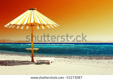 Wood umbrella on beach with clear red sky - stock photo