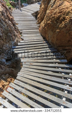 wood walk way in to the rock way - stock photo