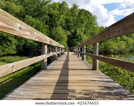 Wood walkway, over a river. low down perspective.