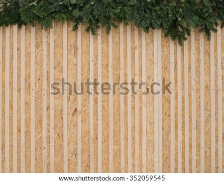Wood wall with an evergreen branches wreath - stock photo