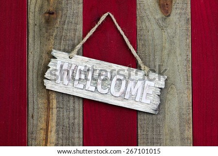 Wood welcome sign hanging on antique red and wooden rustic background - stock photo