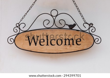 wood welcome sign hanging on wall of restaurant - stock photo