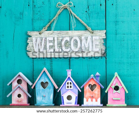 Wood welcome sign hanging over row of colorful spring birdhouses with antique teal blue rustic wooden background - stock photo