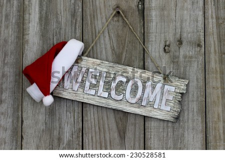 Wood welcome sign with Christmas Santa Claus hat hanging on old wooden background - stock photo