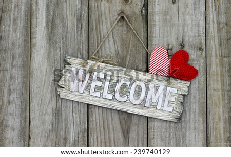 Wood welcome sign with red heart and candy cane striped heart hanging on shabby antique wooden background - stock photo