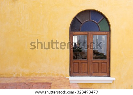 wood window on yellow cement mortar wall background - stock photo