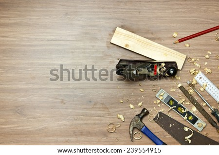 Wood working tools, used in carpentry by a carpenter background. Assorted items, such as a hammer, a wood saw, a spirit level, rasp, screw driver, a carpenter's square and pencil,  - stock photo
