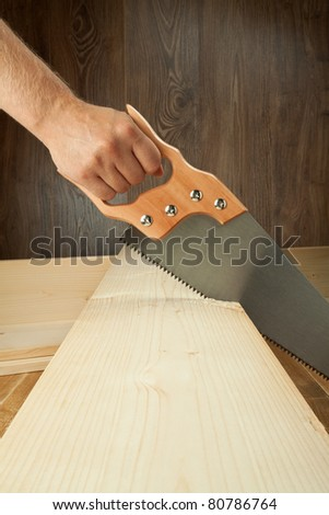 Wood workshop. Carpenter cutting plank with hand saw. - stock photo
