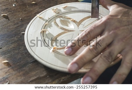 Woodcarver makes threaded plate. Wooden plate. Bulgaria, Plovdiv - stock photo