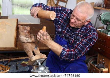 Woodcarver work in his workshop. Shallow depth of field. - stock photo