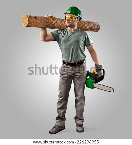 woodcutter in helmet with chain saw and log on  grey background - stock photo