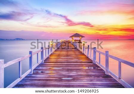 Wooded bridge in the port between sunrise. - stock photo